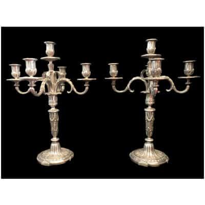 Paire de candélabres à cinq feux en bronze ciselé et argenté à décor de cannelures rudentées, guirlandes, feuillages.