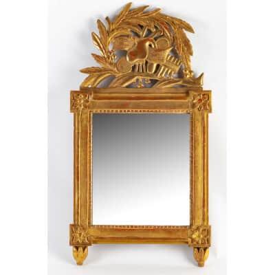 Petit miroir à fronton en bois sculpté et doré à décor d'attributs de musique époque Louis XVI